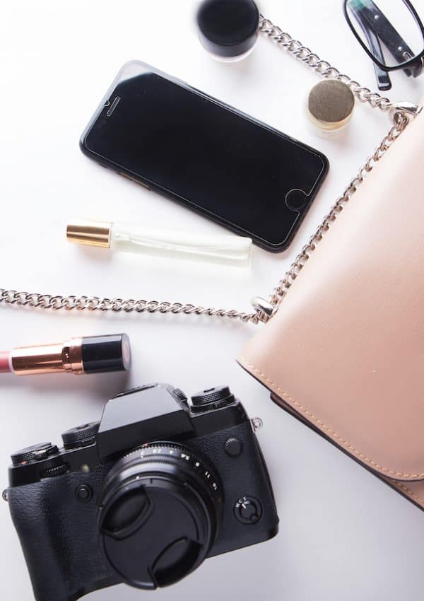 top-view-of-woman-beige-bag-with-accessories-smartphone-cosmetics-lasses-camera-and-perfume-on-white-background
